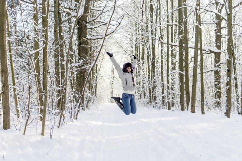 Dziewczyna w drewnach skacze up Mnóstwo śnieg fotografia stock