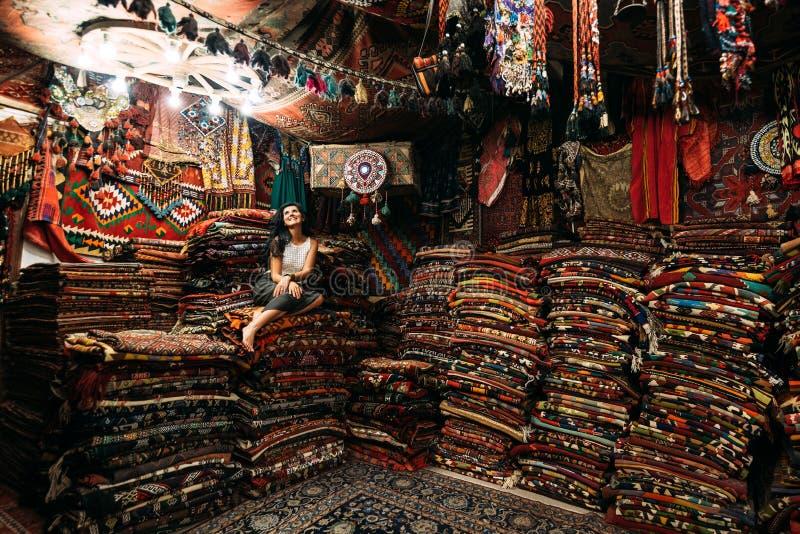 Dziewczyna w dywanowym sklepie Szcz??liwy kobieta klient wybiera barwionego dywan w dywanowym sklepie Dziewczyna w turecczyzna ry zdjęcie stock