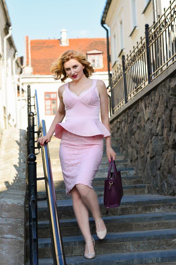 Dziewczyna w eleganckim kostiumu z kiesą chodzi w górę schodków w starym miasteczku zdjęcie royalty free