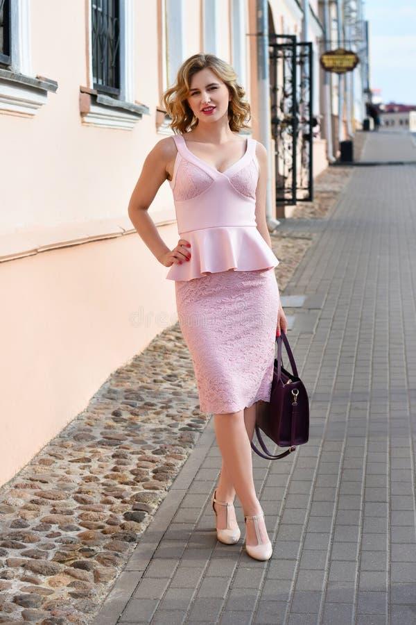 Dziewczyna w eleganckim kostiumu z kiesą chodzi wokoło starego dziejowego miasta zdjęcia royalty free