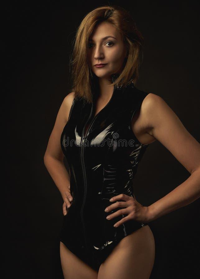 Dziewczyna w erotycznym portrecie Rzemiennego seksownego kostiumu płci bawić się gry czarny t?o portret fotografia royalty free