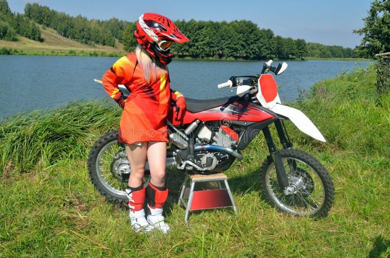 Dziewczyna w hełma kosztach o motocyklu motocross obraz royalty free