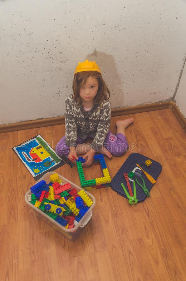 Dziewczyna w hełmie budowniczy zbiera projektanta zdjęcie stock
