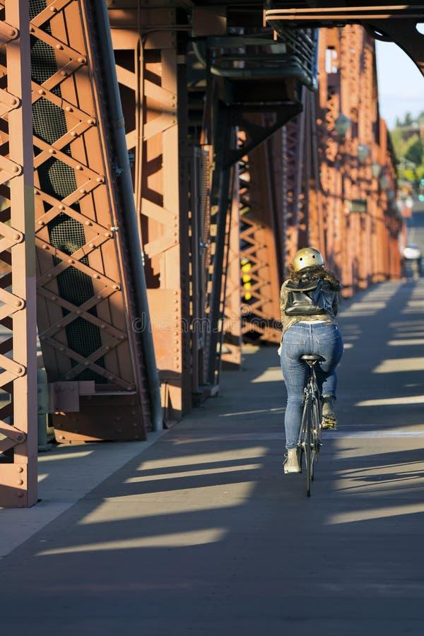 Dziewczyna w hełmie z plecak jazdy rowerem na moście i zdjęcie royalty free