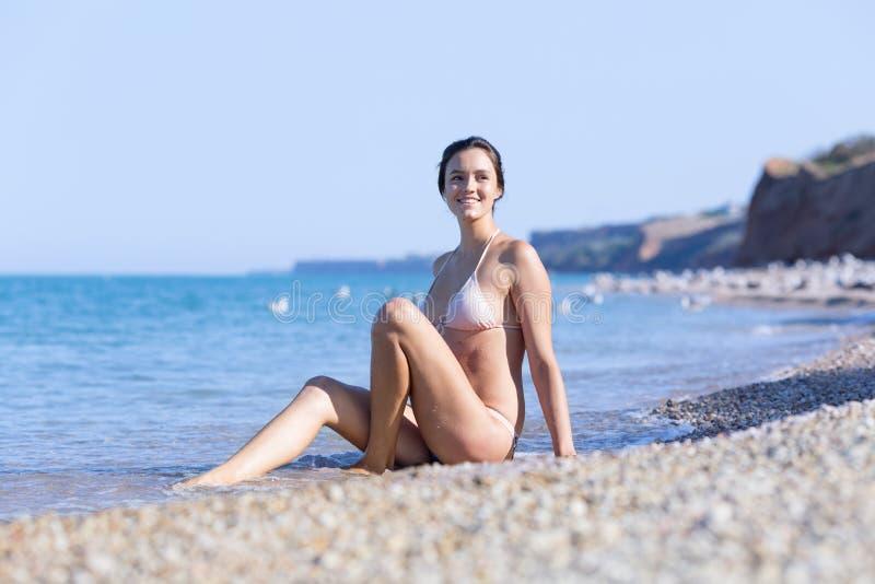 Dziewczyna w jasnoróżowym swimsuit obsiadaniu na otoczakach zbliża morze zdjęcia stock