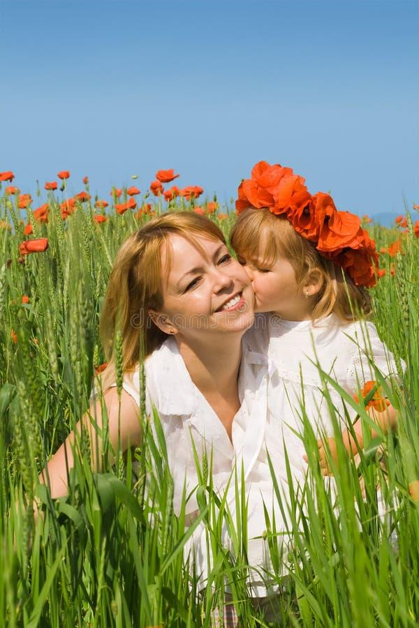 dziewczyna w jej całować mały matka poppy fotografia royalty free