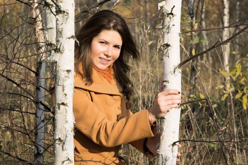 Dziewczyna w jesień dniu wśród młodych drzew obraz royalty free