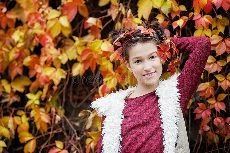 Dziewczyna w jesień parka mienia żółtym liściu klonowym w ręce zdjęcie royalty free
