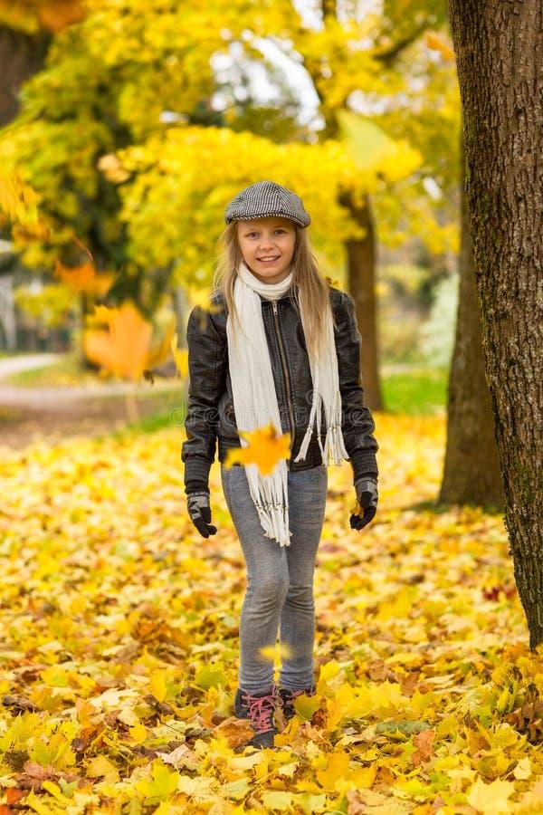 Dziewczyna w jesień parku spada liściach i zdjęcie royalty free