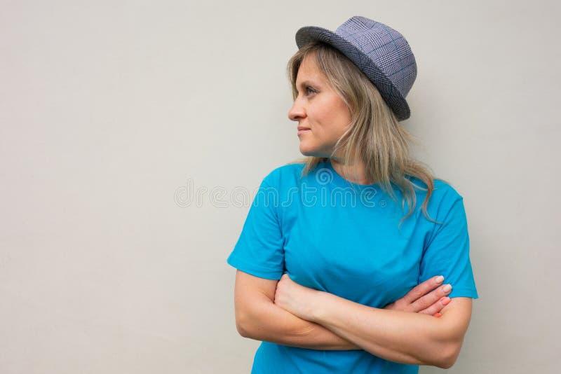 Dziewczyna w kapeluszu Biała w średnim wieku kobieta patrzeje oddalonych, krzyży rękami i obracającą głową i pozytywną twarzą na  zdjęcie stock