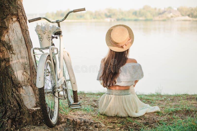 Dziewczyna w kapeluszu siedzi na brzeg rzeki obraz stock