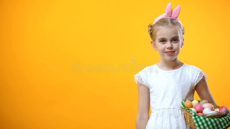 Dziewczyna w kapitałki mienia koszu Wielkanocni jajka, pomarańczowy tło, statystyki obrazy stock
