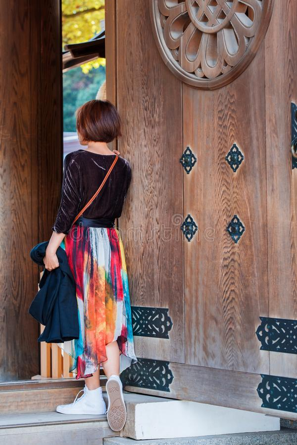 Dziewczyna w kolorowej spódnicie blisko drewnianych drzwi świątynia, Tokio, Japonia pionowo zdjęcie stock