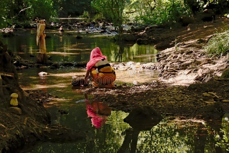 Dziewczyna w kolorowych płócien siedzącym puszku obok rzeki w lesie fotografia stock