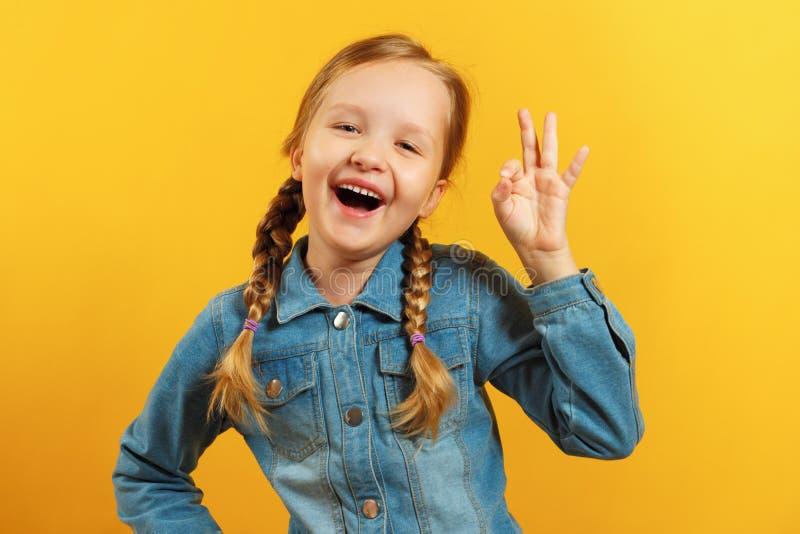 Dziewczyna w koszulce dżinsu na żółtym tle Dziecko pokazuje znak OK Koncepcja sukcesu, zatwierdzenie zdjęcia stock
