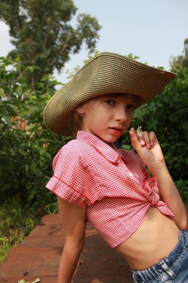 Dziewczyna w kowbojskiego kapeluszu obsiadaniu w ogródzie 20353 fotografia stock