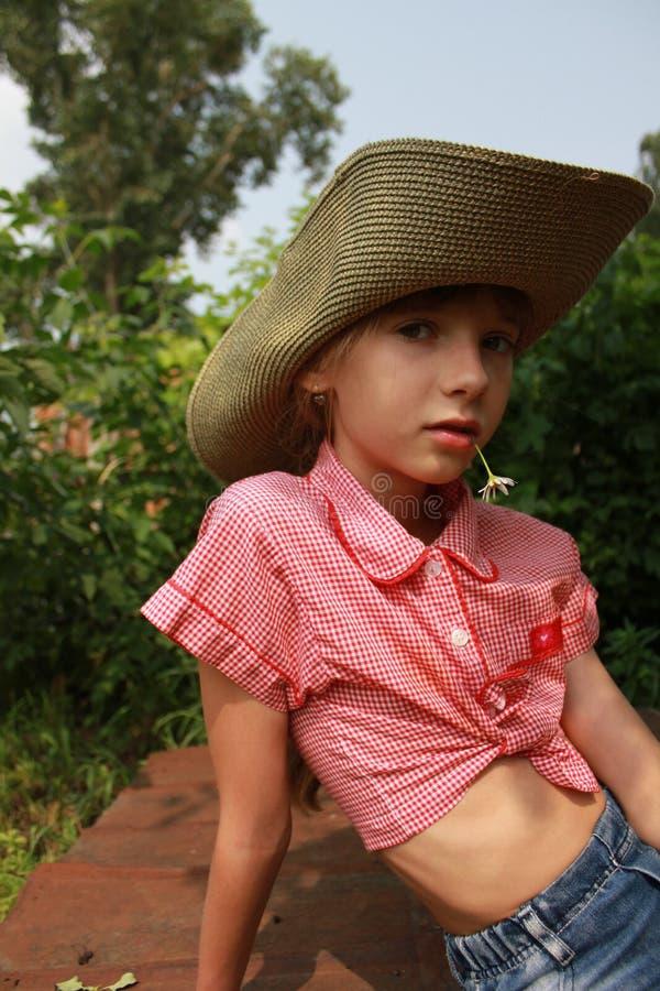 Dziewczyna w kowbojskiego kapeluszu obsiadaniu w ogródzie 20355 obrazy royalty free