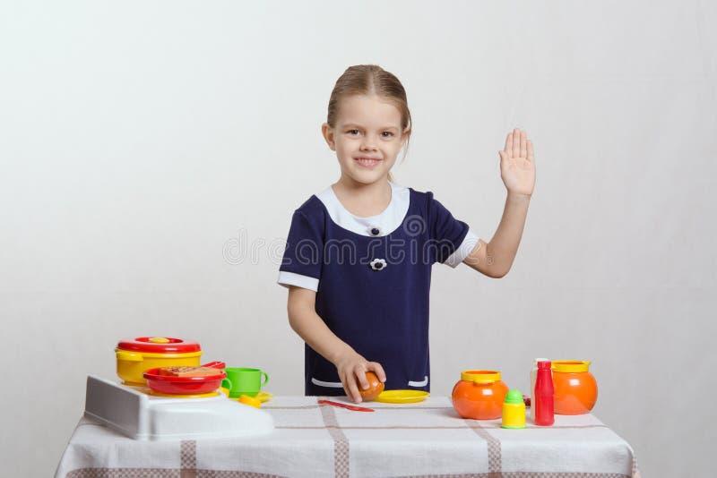 Dziewczyna w kuchennym falowaniu do widzenia obrazy royalty free