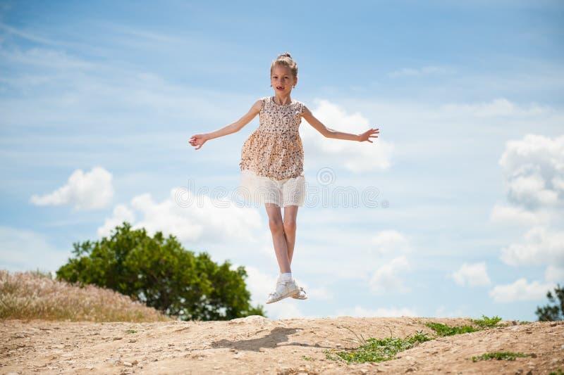 Dziewczyna w lato sukni doskakiwaniu w tancerz pozyci przeciw tłu piękny niebo i drzewa zdjęcia stock
