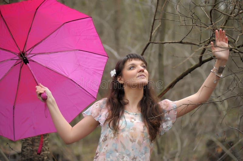 Dziewczyna w lekkiej sukni z r??owym parasolem w parku obrazy royalty free