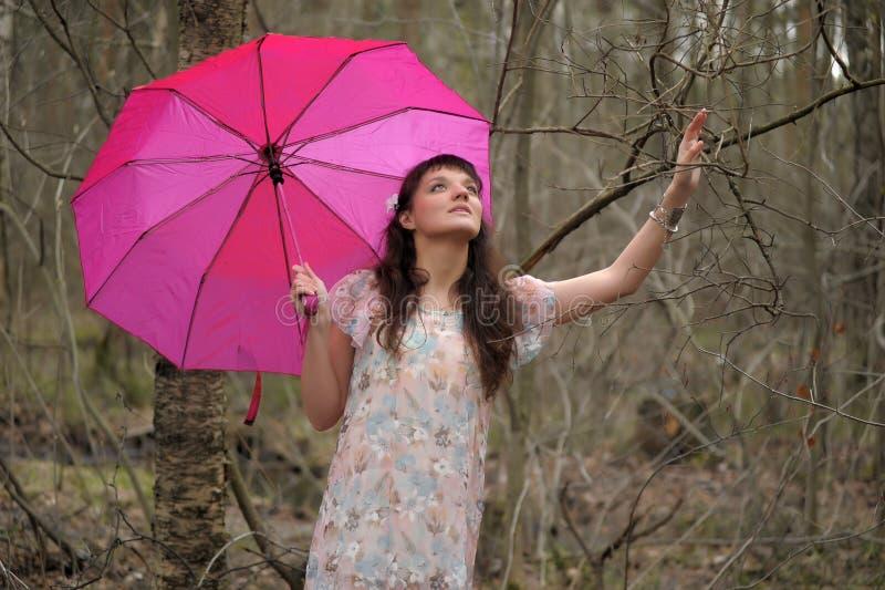 Dziewczyna w lekkiej sukni z r??owym parasolem w parku zdjęcie stock