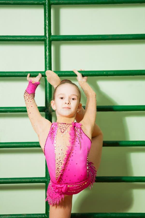 Dziewczyna w leotard ćwiczy gimnastykach na ściennych barach zdjęcia royalty free