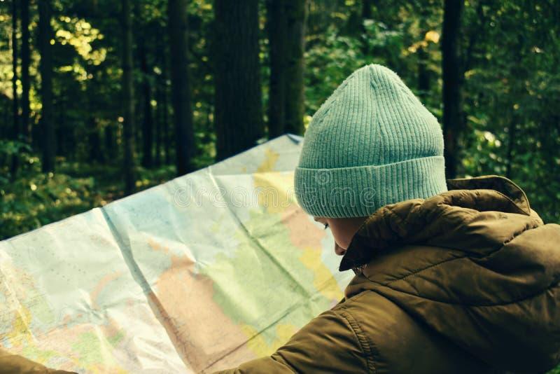 Dziewczyna w lesie z mapą geograficzną Orientacja zdjęcia royalty free