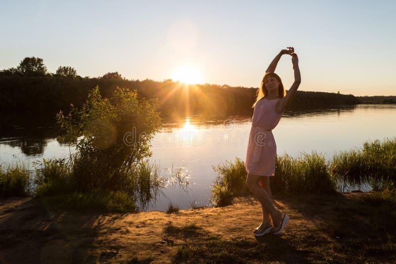 Dziewczyna w menchiach ubiera na rzeki plaży podczas zmierzchu Plenerowy portreta i słońca tło zdjęcie stock