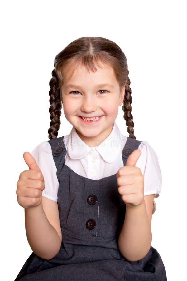 Dziewczyna w mundurkach szkolnych pokazuje aprobaty obrazy stock