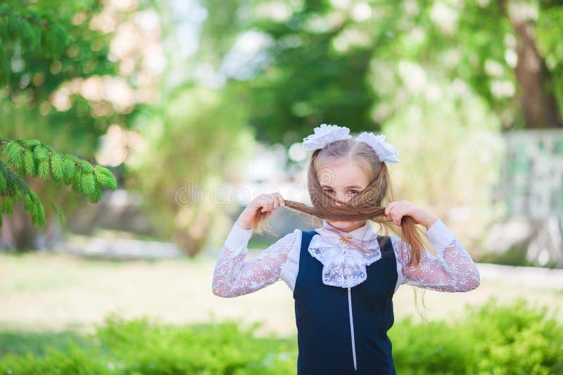 Dziewczyna w mundurku szkolnym rozprzestrzenia ona i raduje się przy ukończeniem szkoła ręki uczennica raduje się na początku sch zdjęcie royalty free