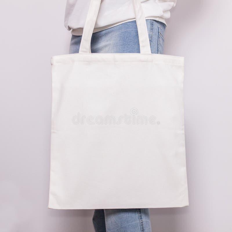 Dziewczyna w niebieskich dżinsach trzyma pustą bawełnianą eco dużego ciężaru torbę, projekta mockup Handmade torba na zakupy dla  fotografia stock