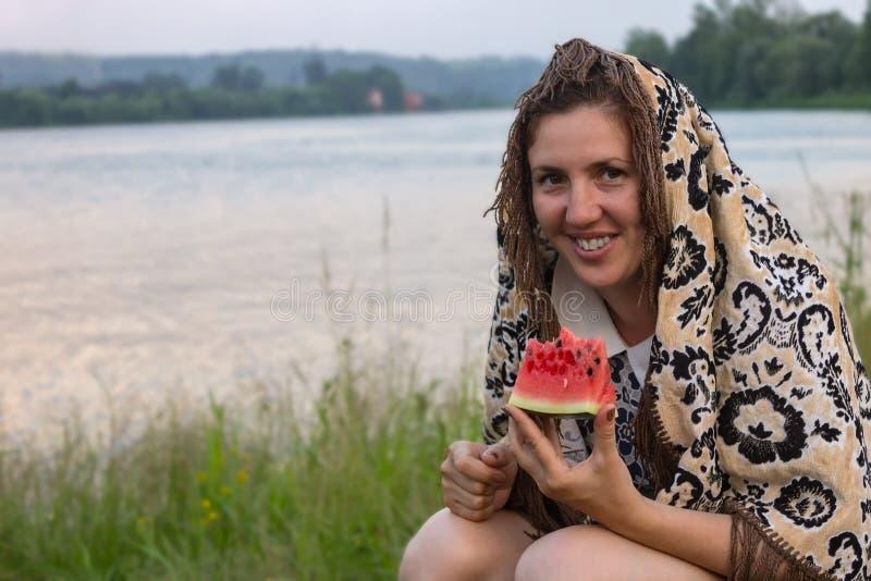 Dziewczyna w obywatelów ubraniach zaludnia wschodni stepów chwyty arbuza blisko rzeki zdjęcia royalty free