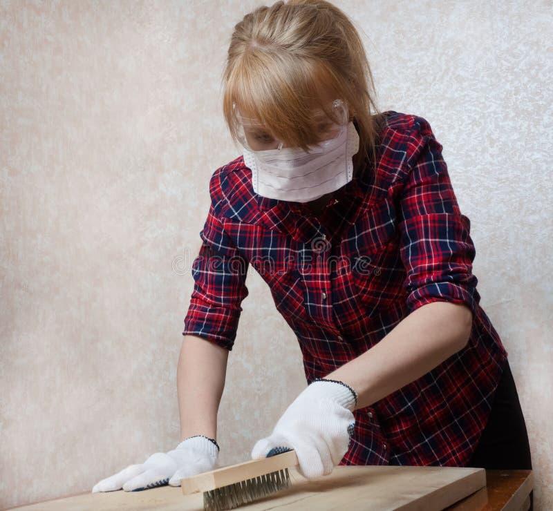 Dziewczyna w ochronnych szkłach, masce i rękawiczkach, pracuje na powierzchni drewniana deska zdjęcia stock