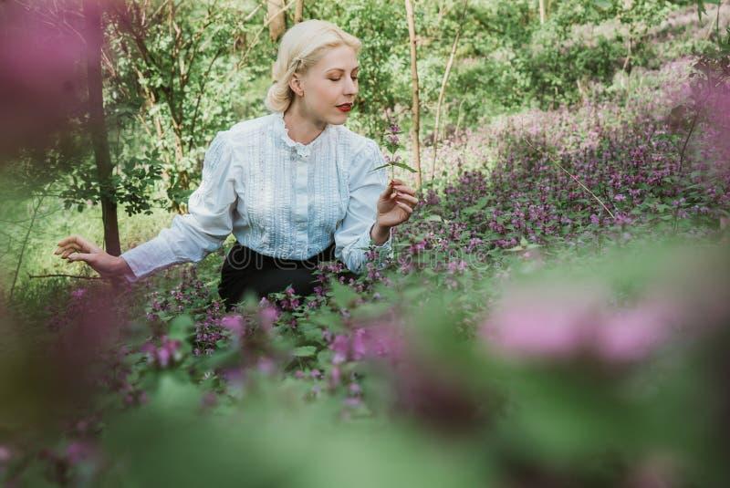 Dziewczyna w ogródzie zbiera ziele i obwąchuje kwiaty obraz stock