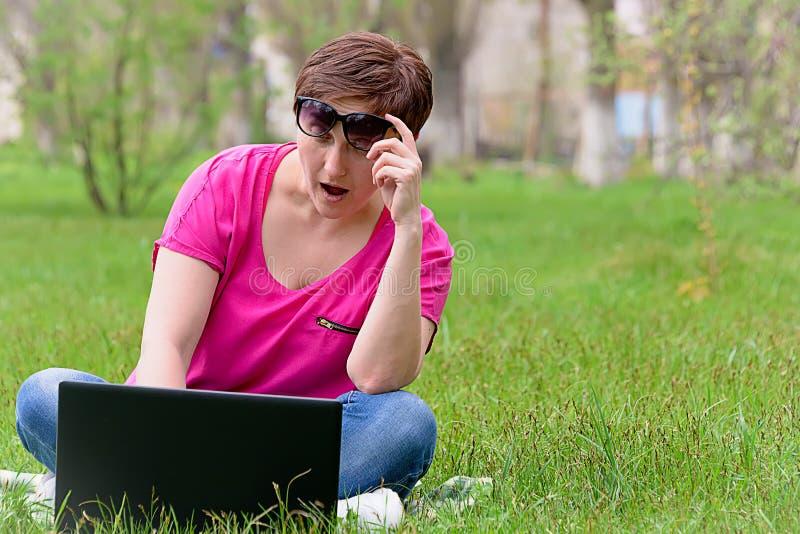 Dziewczyna w okularach przeciwsłonecznych na zielonej trawie obrazy stock