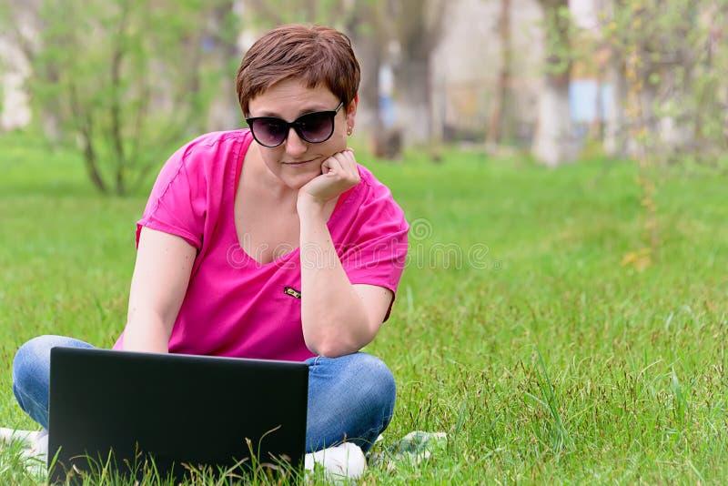 Dziewczyna w okularach przeciwsłonecznych na zielonej trawie fotografia royalty free