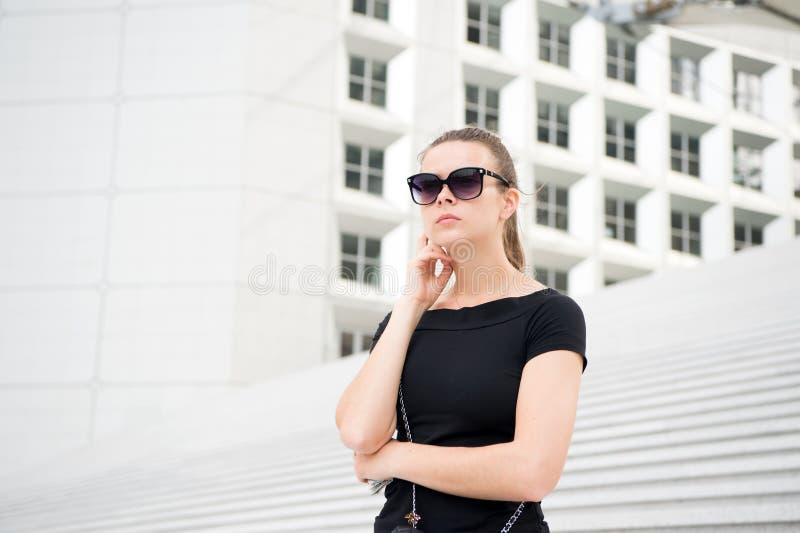 Dziewczyna w okularach przeciwsłonecznych pozuje na schodkach i buduje w Francja obraz royalty free