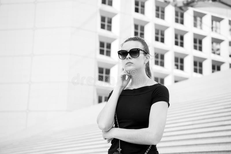 Dziewczyna w okularach przeciwsłonecznych pozuje na schodkach i buduje w Francja fotografia stock