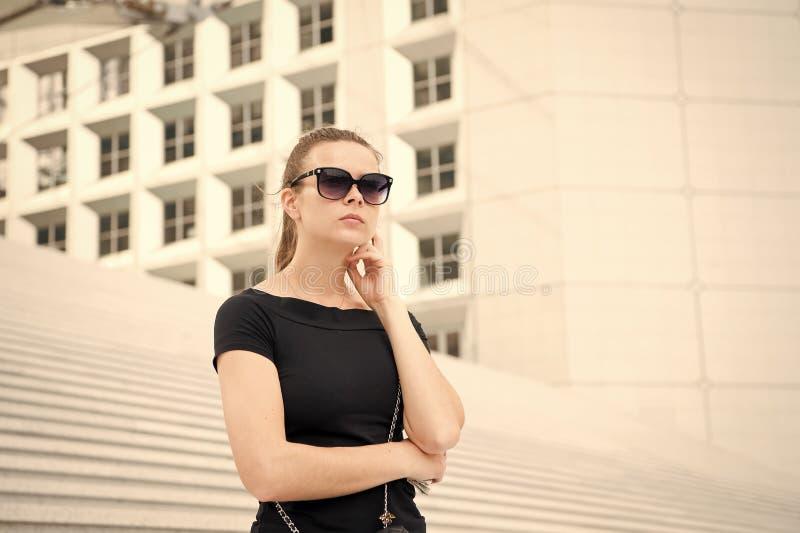 Dziewczyna w okularach przeciwsłonecznych pozuje na schodkach i buduje w Francja zdjęcia royalty free
