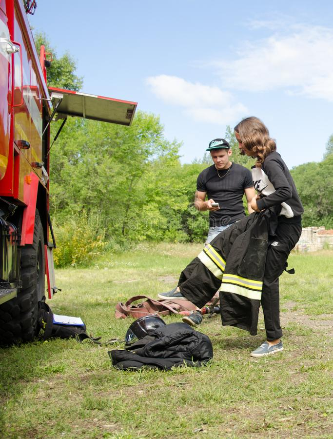 dziewczyna w palacza ` s kostiumu przeciw pożarniczemu silnikowi przygotowywa pokonywać przeszkoda kurs obraz stock