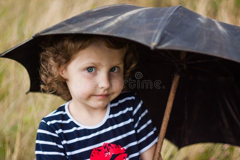 Dziewczyna w pasiastej koszulce z czarnym parasolem w polu obrazy stock