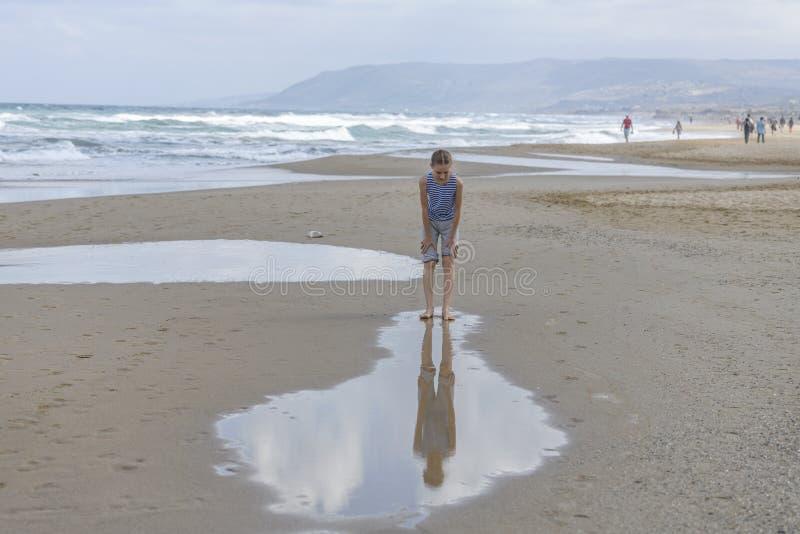 Dziewczyna w pasiastym koszulka bieg wzdłuż plaży obraz stock