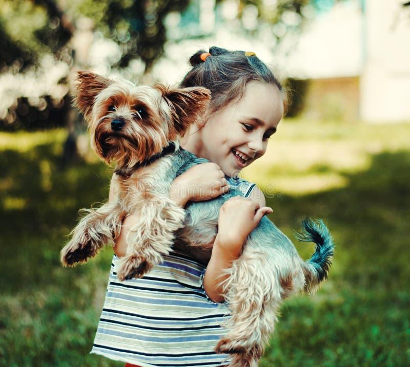 Dziewczyna w pasiastym pulowerze uśmiecha się małego psa i trzyma zdjęcia stock