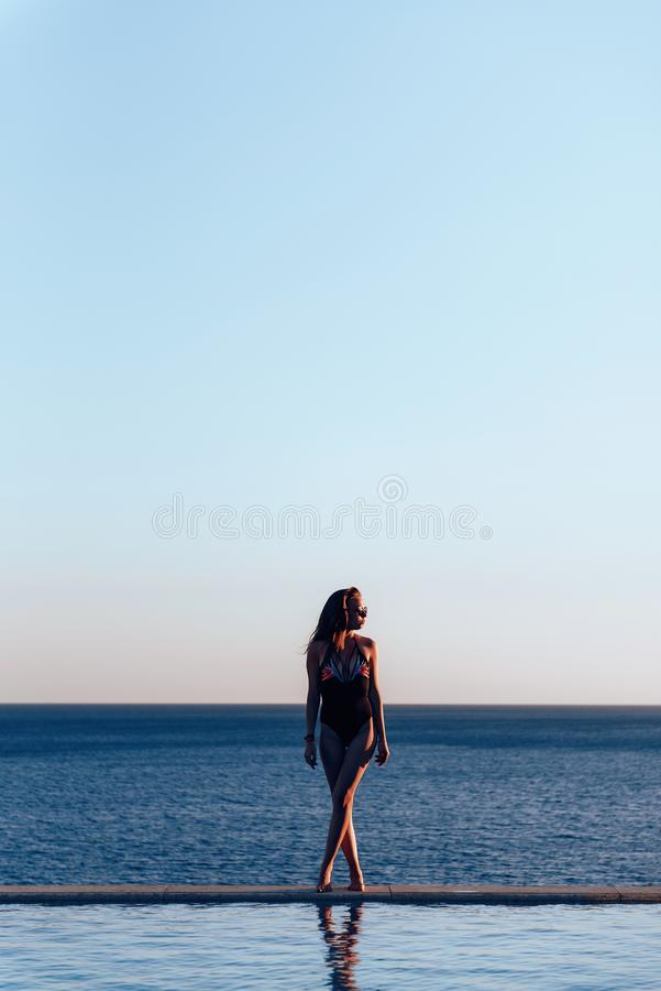 Dziewczyna w pięknym kostiumu kąpielowym przy zmierzchem dennymi mienie okularami przeciwsłonecznymi obrazy royalty free