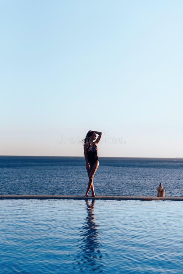 Dziewczyna w pięknym kostiumu kąpielowym przy zmierzchem dennymi mienie okularami przeciwsłonecznymi zdjęcia royalty free