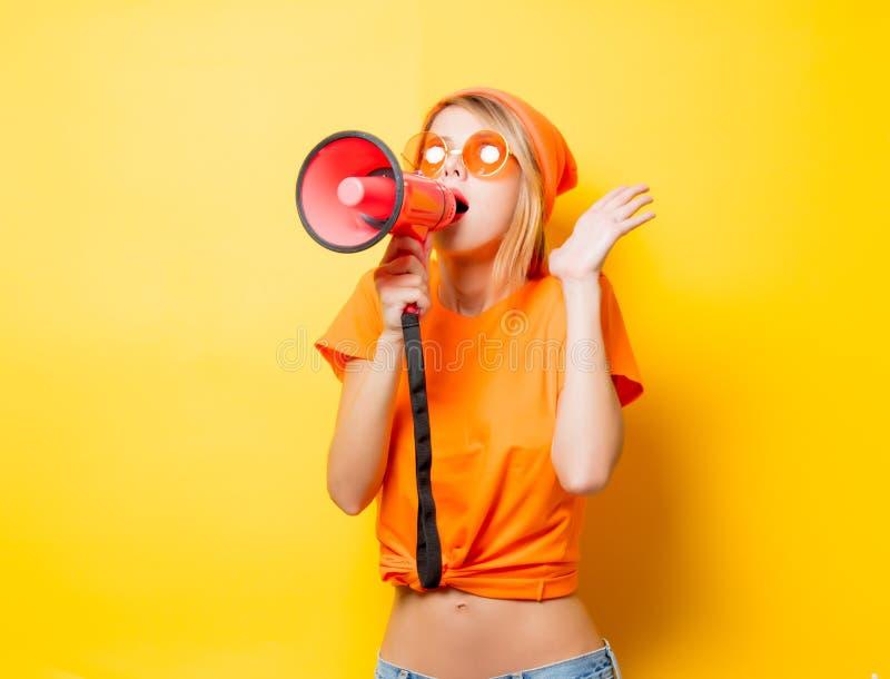 Dziewczyna w pomarańcz ubraniach z różowym megafonem obraz stock