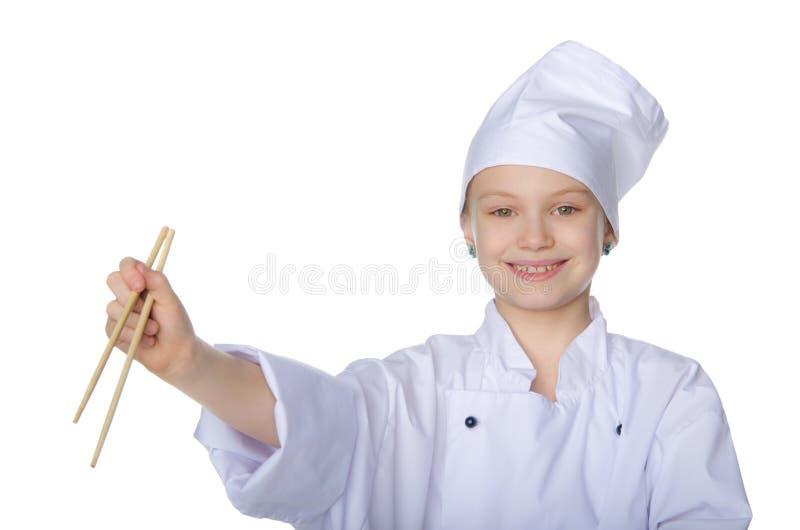 Dziewczyna w postaci szefa kuchni z chopsticks zdjęcie stock