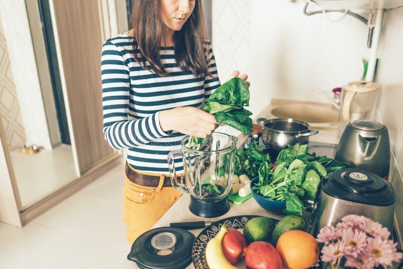 Dziewczyna w przypadkowej odzieży w kuchni przygotowywa zielonych świeżych produkty dla smoothie fotografia stock