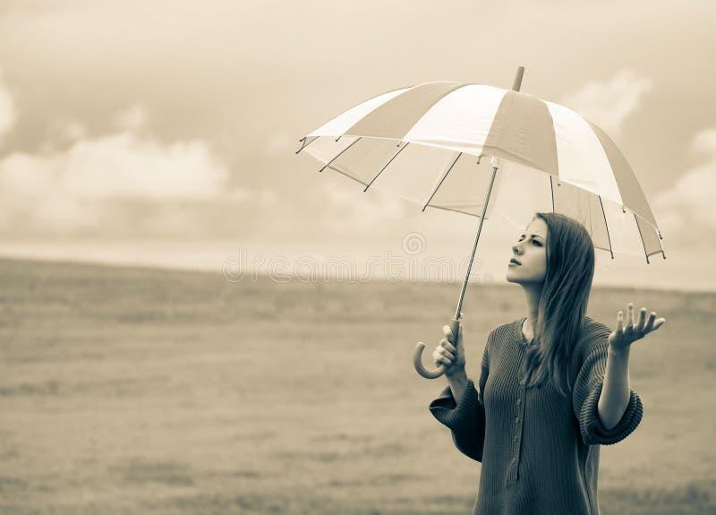 Dziewczyna w pulowerze z parasolem przy pszenicznym polem obraz stock