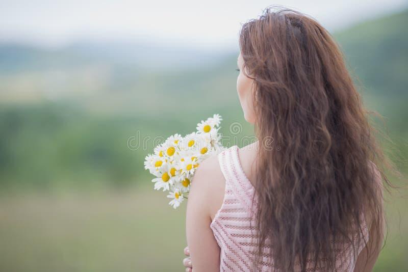 Dziewczyna w różowej sleeveless sukni z bukietem chamomile zdjęcia royalty free